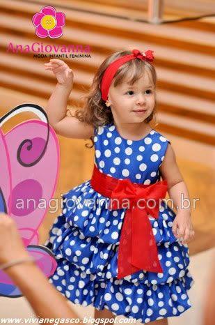 O vestido da Galinha Pintadinha vêm com três saias em camadas sobrepostas e laço vermelho na cintura.