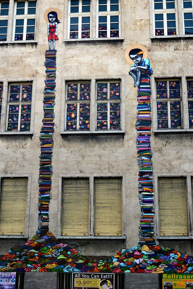 Brazilian street artist Walter Nomura aka Tinho is currently in Frankfurt, Germany where he just finished working on this brilliant new piece. Invited by Schirn for the Street Art Brazil exhibition, the talented artist painted this piece depicting two children waiting on a pile of books.