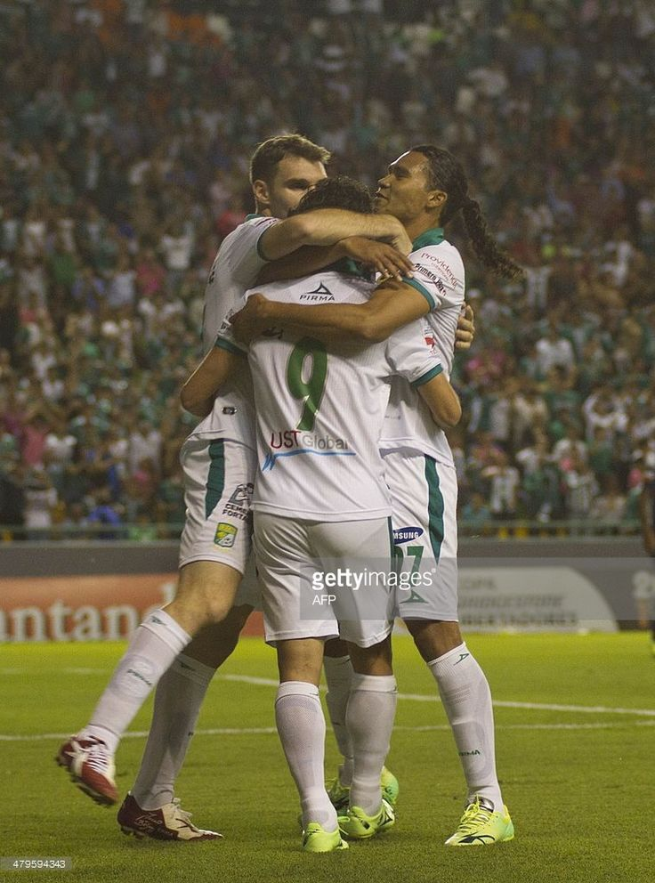 Matias Britos (C) of Leon celebrates his goal against Ecuador's Emelec with teammates Mauro Boselli (L) and Carlos Pena (R) during their Copa Libertadores football match on March 19, 2014 in Leon, Mexico.