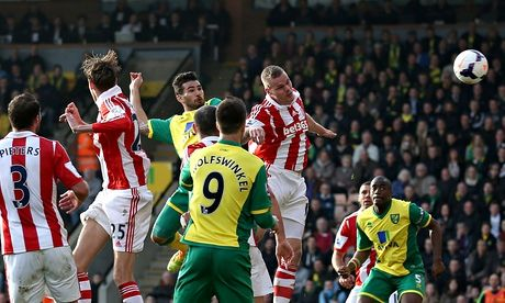 Norwich City's Bradley Johnson, centre, jumps to score the opening goal against Stoke City in the Premier League at Carrow Road.