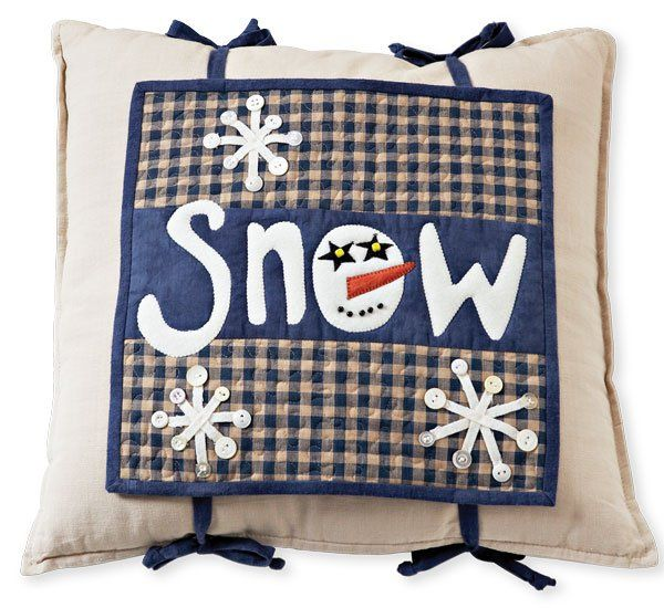 A whimsical pillow topper features applique and winter motifs.