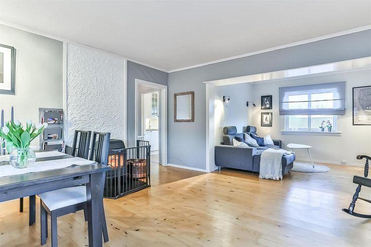 Lys grå stue. Witte muur achter de kachel