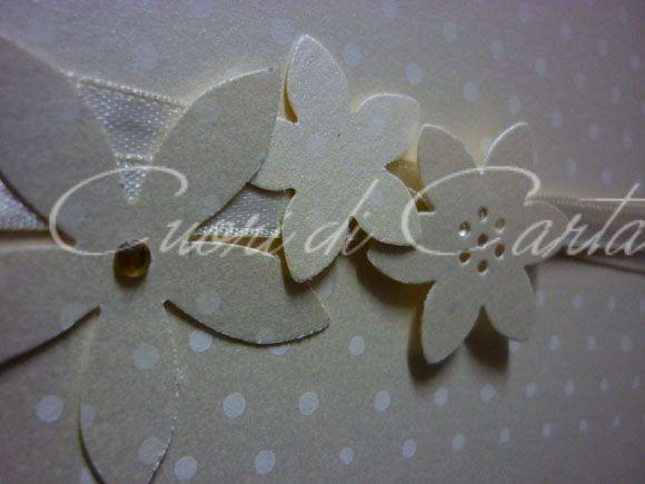 Particolare partecipazione scritta a mano, carta perlata decorata con pois, nastro in raso e fiorellini in carta.