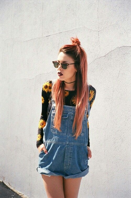 dyed hair and denim dungarees with a patterned jumper.