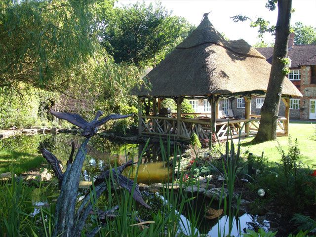 Lapa with thatched roof and rustic timber poles in a garden setting Includes BBQ and furniture.