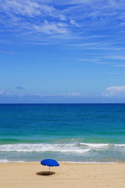 San Juan, Puerto Rico - empty beach, blue umbrella, clear skies
