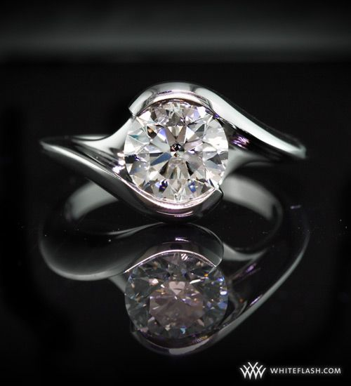 """This platinum """"Iris"""" Solitaire Engagement Ring features a beautiful bypass design and holds a gorgeous 1.5ct Whiteflash A Cut Above Diamond."""
