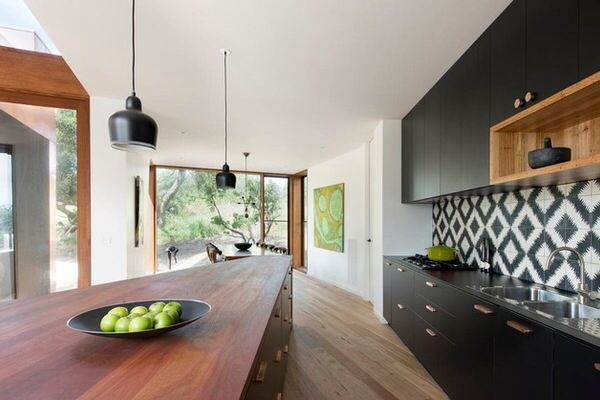 Achromatic patterned tile splash back with matte black cabinets and timber accents. Photo credit- Auhaus Architecture