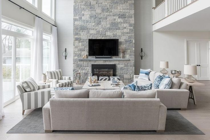 Blue and gray living room features a pair of light gray linen sofas lined with blue pillows face a gray wash cocktail table across from a air of gray striped accent chairs.