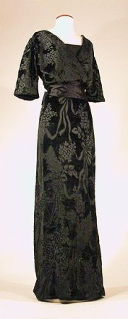 Midnight olive drab voided-velvet gown, ca. 1907. French. Demi-empire faux surplice bodice with elbow-length kimono sleeves. Black tulle modesty, slender skirt with semi-floating back panel, wide black silk satin ribbon belt with self-bow. Size 2-4.