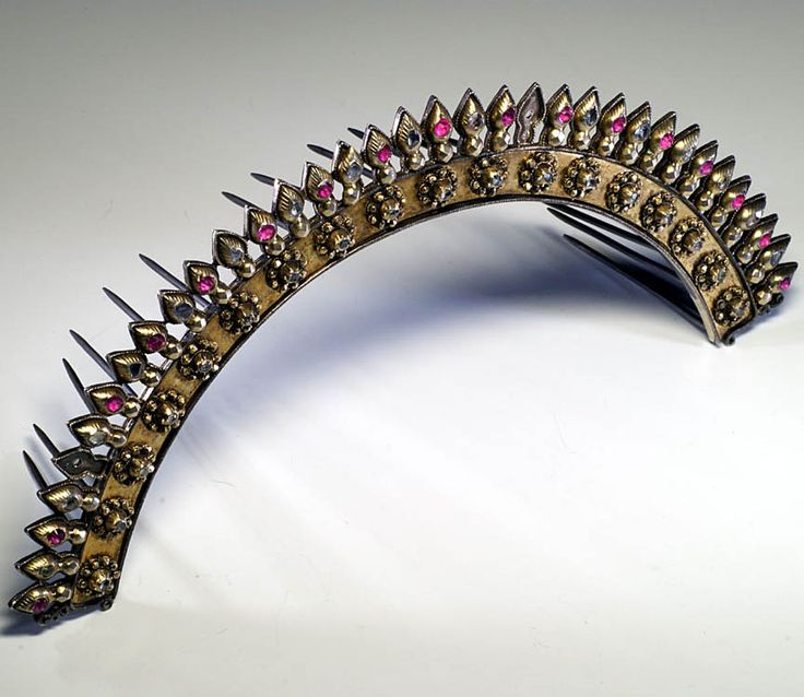 Javanese tiara with precious stones, Indonesia, Width : 1 inch, Height : 5 7/8 inch, Depth : 1 7/8 inch, This gorgeous silver tiara comes from Java. It is probably a part of a headdress more important worn for a wedding. The rich decoration use diamonds and rubis on two rows. early 20th century