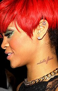 """Bimbo Rihanna got, """"rebelle fleur"""" tattooed in script on the left side of her neck (where else)... it actually translates to """"rebel flower"""" (in the context of a sentence)... however (in French), the adjective usually comes before the noun & the phrase is supposed to read, """"Fleur Rebelle""""... but, """"shee jest splainz"""" it away by incorrectly citing, """"Rebelle Fleur translates to rebel flower, NOT rebellious flower... itz too nouns... sew in dat case 'fleur' don't HAVE tuh bee fust""""..."""