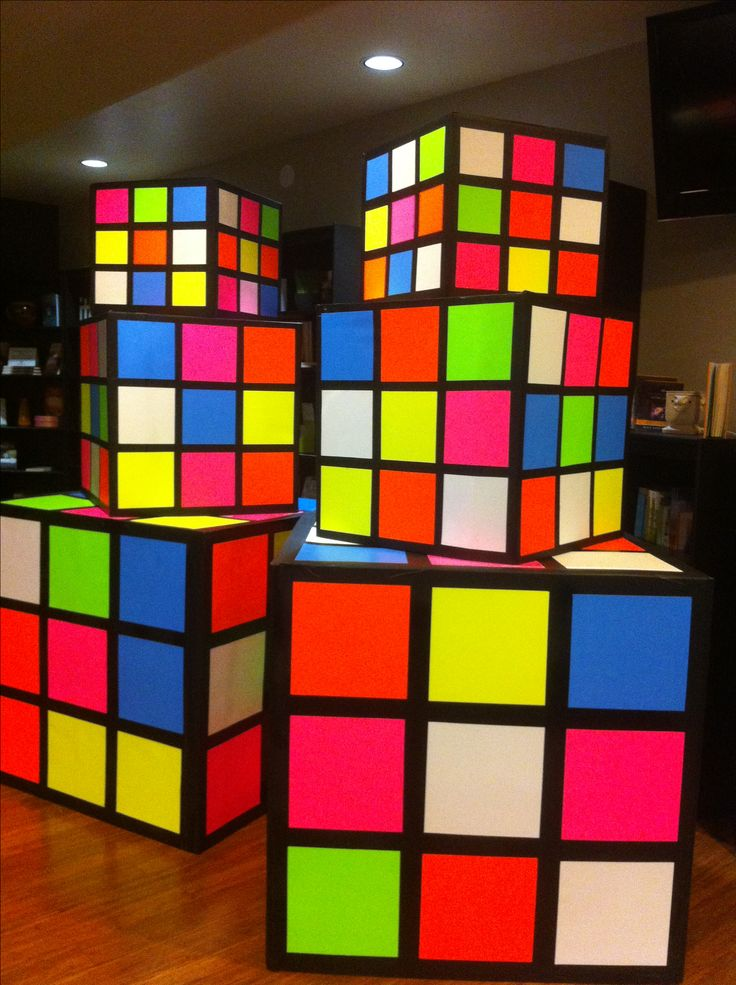 Rubik's cubes made from refrigerator boxes, black primer paint, spray adhesive and neon poster board from the .99 store.