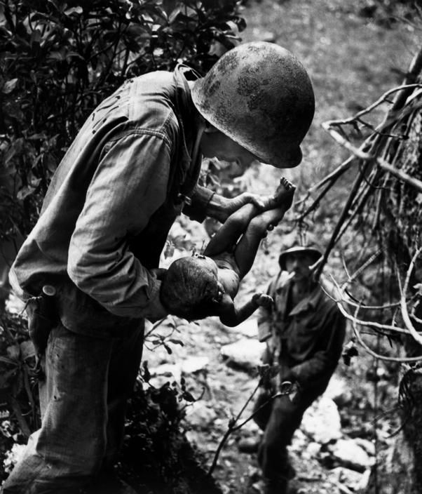 .WORLD WAR II. The Pacific Campaign. June 1944. Battle of Saipan Island. US Marine holding a wounded and dying baby found in the mountains - Photo W. Eugene Smith