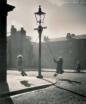 Children in the 1950s make their own fun with a makeshift swing from a lamppost.  Photo credit: Karl Hughes Arps