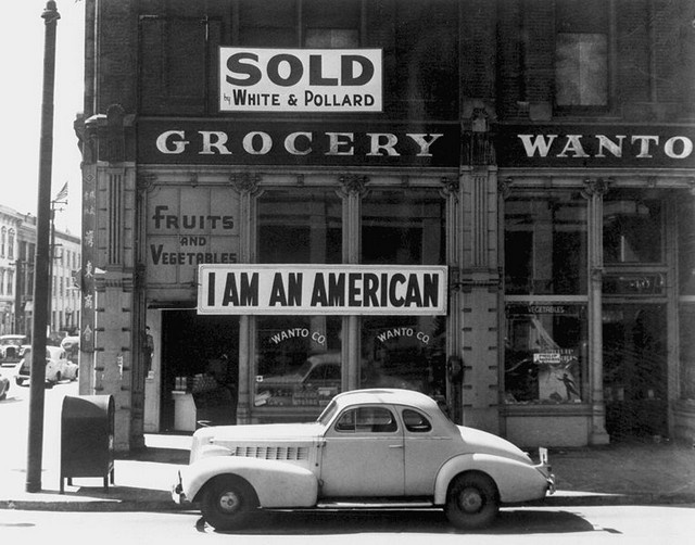 "Dorothea Lange's previously unpublished photo series on the internment of US citizens of Japanese ancestry in the 1940s. The grocery store in this photo was owned by a Japanese-American. Lange took the photo of his his ""I Am An American"" banner shortly before he was relocated to an internment camp."