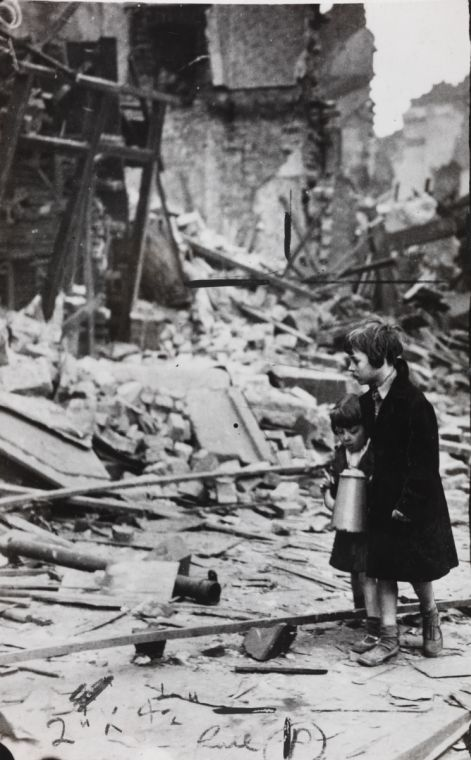 A photograph entitled 'Kiddies walk through wreckage of their homes at Liverpool', taken in 1941 by an unknown photographer for the Daily Herald.    The Liverpool Blitz of 1941 involved 681 Luftwaffe bombers. 2315 high explosive bombs and 119 other explosives were dropped on the city. There were 2895 casualties, with many more people left homeless.