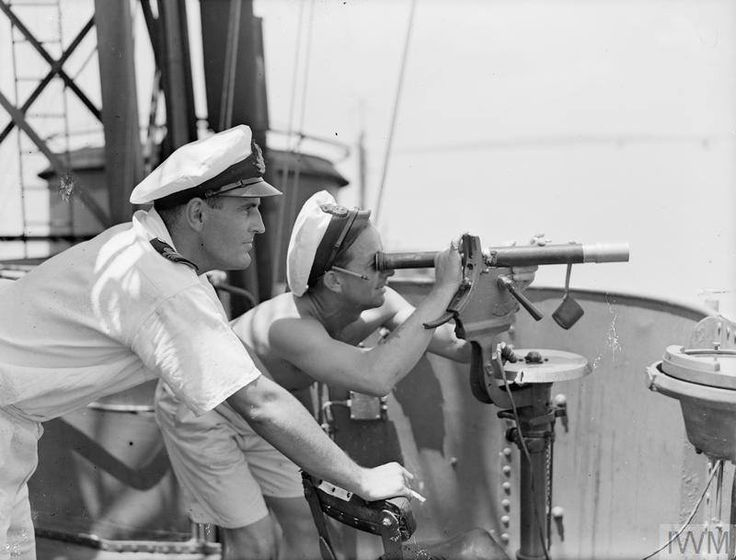Lt-Cdr PW Stewart, Gunnery officer of the 6th Destroyer Flotilla, and the Chief Yeoman of Signals check fall of shot from the destroyers' guns, on Indonesian nationalist positions. Surabaya, Java. 16th November 1945.  Note: The three destroyers from the 6th Destroyer Flotilla, involved in this action were HMS CAESAR, HMS CAVALIER and HMS CARRON.