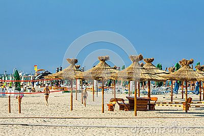 MAMAIA, ROMANIA - AUGUST 5, 2011: Tourists enjoying a sunny day on the beach in Mamaia seaside summer resort, Romania. Mamaia is Romanias biggest seaside resort of 350m width and 8.5km length in the north-east of Constanta city on the coast of the Black Sea.