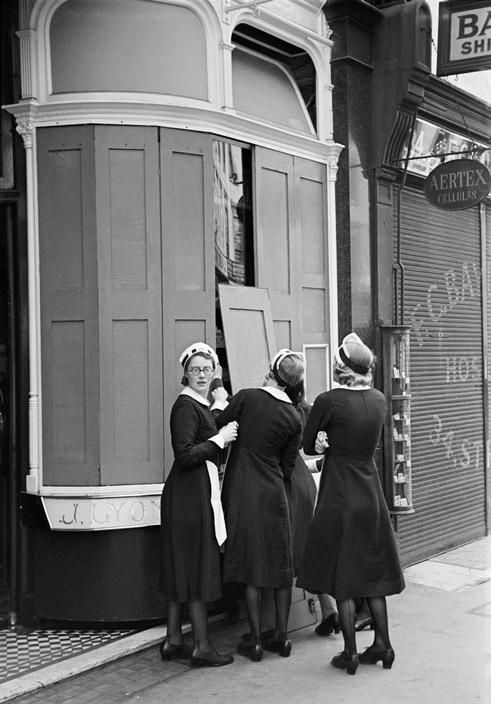 """George Rodger  GB. London. World War II. The Blitz. """"Nippies"""" (Lyons teashop waitresses) remove protective shutters from windows in early morning. 1940."""