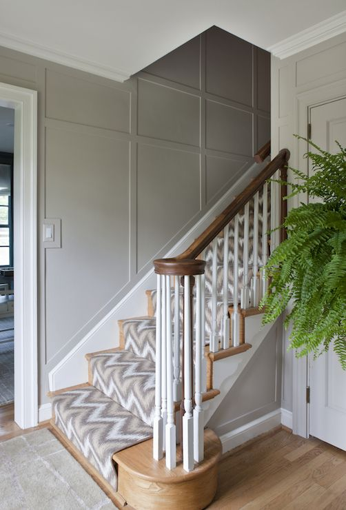Contemporary foyer with gray paneled walls framing staircase dressed with yellow and gray ikat stair runner.
