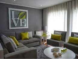 Decoración de sala con paredes y muebles grises que crean un ambiente sobrio muy elegante iluminado con cojines en verde pera.
