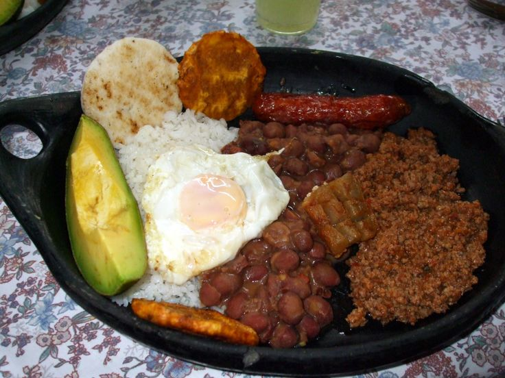 """""""Bandeja Paisa"""" Typical dish from Medellin, includes white rice, red beans, avocado, fried egg, sausage, pork, corn bread, and fried plantain."""