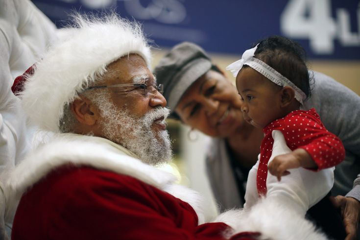 African American Santa Claus Langston Patterson (L), 77, greets four-month-old Raelyn Price as her grandmother Gloria Boissiere looks on, at Baldwin Hills Crenshaw Plaza mall in Los Angeles, California, December 16, 2013. Patterson has worked as Santa since 2004 at the mall, which is one of the few in the country with a black Santa Claus. A New Mexico teacher who told an African American student that Santa Claus was white has been put on paid administrative leave, an official said on…