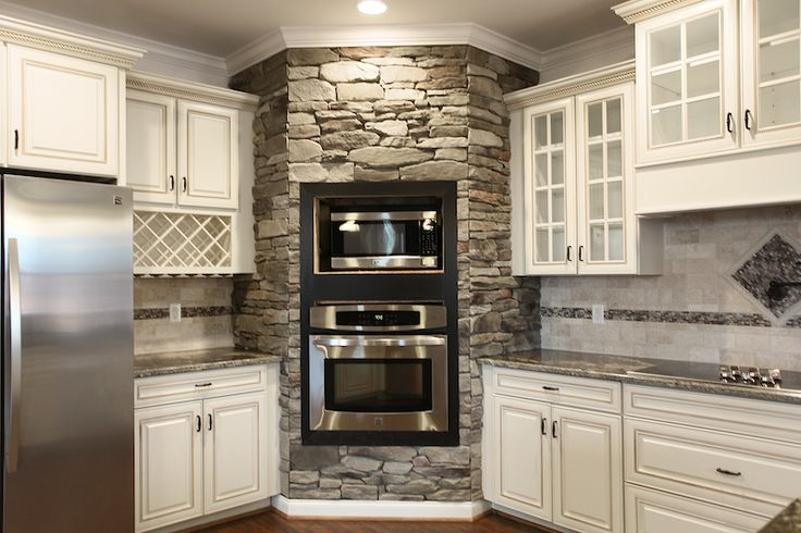 Lynchburg real estate photography virtual tours photo of a rustic kitchen with white French country style cabinets, glass windows, stacked stone. Love all the glass doors on these cabinets!