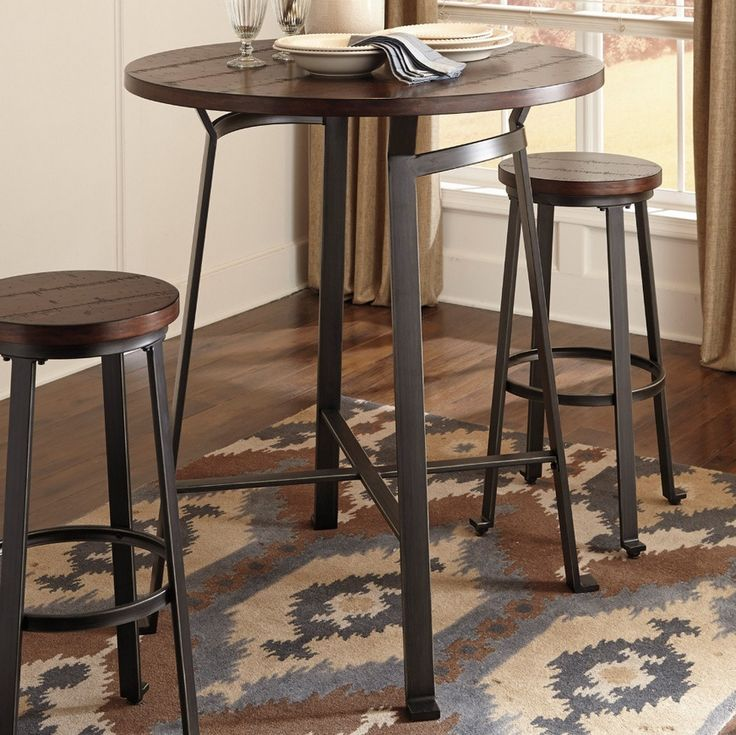 Industrial inspired round pub table with bar shaped tubular metal frame base blackened pewter finish. Brown planked pine veneer tabletop cross saw distressing.