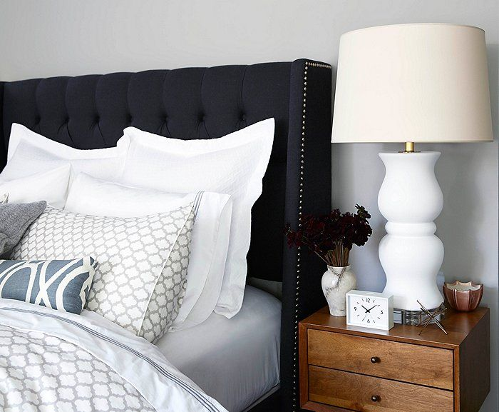 Instead of trying to hide the bed in a studio apartment,Twilley makes it a focal point with a chic upholstered headboard, dove-gray trellis-print pillows, and crisp white sheeting.