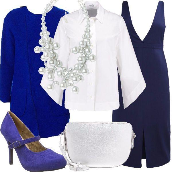 Una camicia bianca dalle linee particolari, con maniche ampie e colletto all'italiana. Indossiamo, sopra, l'abito blu con gonna a tubino. Copriamo il tutto, indossando il cappotto color blu cobalto, con scollo tondo, in lana. Abbiniamo scarpe blu cobalto, con tacco alto, borsa a tracolla, color argento e collana multifilo con perle sintetiche.