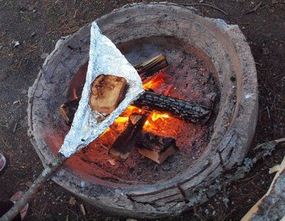 making grilled ham and cheese while camping using a stick and aluminum foil