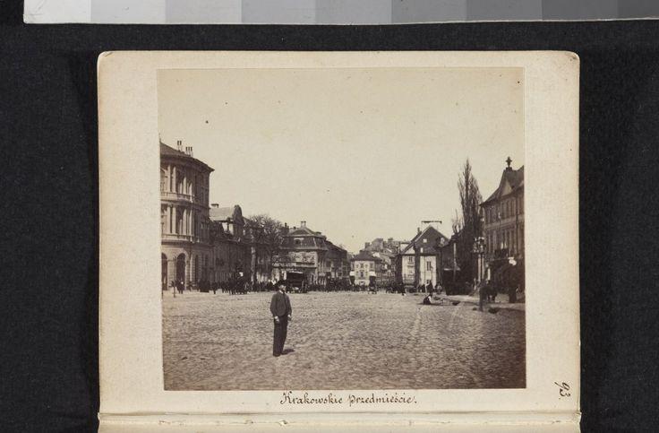 Widok w kierunku północnym z jezdni Krakowskiego Przedmieścia na wysokości kościoła PP Wizytek. Po prawej kamienica, w której Karol Beyer prowadził zakład fotograficzny od września 1857 do maja 1867. Zdjęcie pochodzi z 1861 roku.