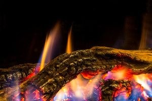 Heatmaster Seamless Gas Fireplace - Close up of Log. This landscape fireplace is available with an Australian drift wood log set, and comes standard with a programmable thermostat remote control and Wi-Fi capability.