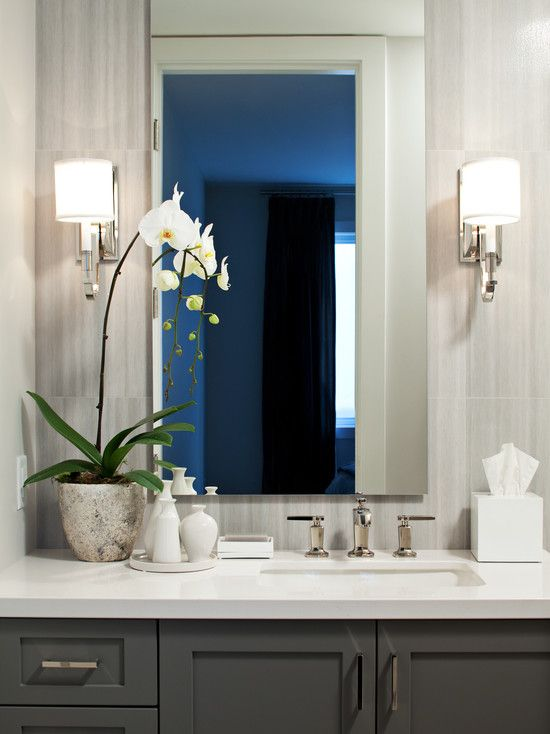 Art Exhibition dark grey cabinets white tops use of sconces
