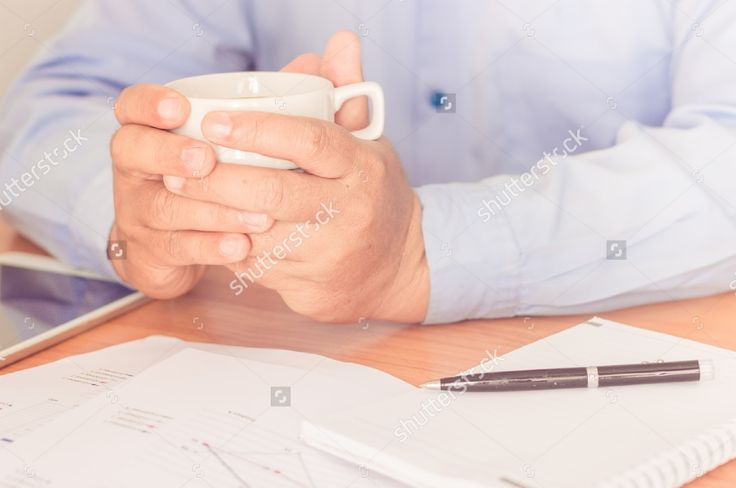 Businessman working on office desk. Writing something on notebook.Holding a coffee cup in a hand. Blurred background, Vintage concept. #business #businessman #man #professional #office #background #notebook #coffee