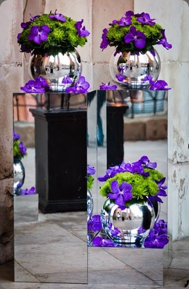 Purple and green floral arrangements sitting atop mirrored stands ☆ Purple and green wedding decorations