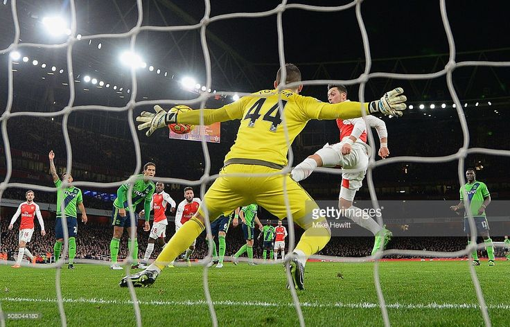 Fraser Forster of Southampton makes a save a shot by Mesut Ozil of Arsenal during the Barclays Premier League match between Arsenal and Southampton at the Emirates Stadium on February 2, 2016 in London, England.