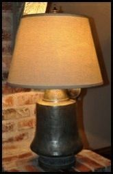 """Mediterranean Jug Lamp $390.00   DESCRIPTION  Neat antique Mediterranean copper jug with lid  converted to table lamp. This is a wonderful piece with lots of history and personality. The lid hangs off to the side and is a fun element that I was able to keep in the design of the lamp. Includes ample cord and finial. Priced w/o shade.  Measurements:  10.5"""" diameter.  18.5"""" to harp base."""