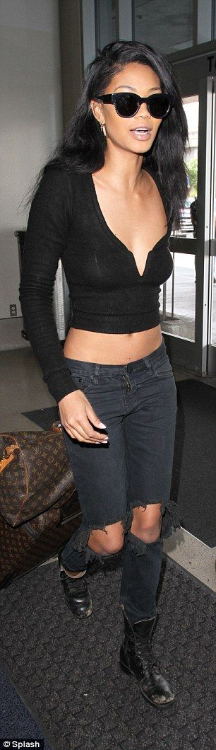 Dare to bare: For her flight, the model swapped out her Coachella-ready cut off short shorts in favour of some jeans but still managed to show off her toned midriff