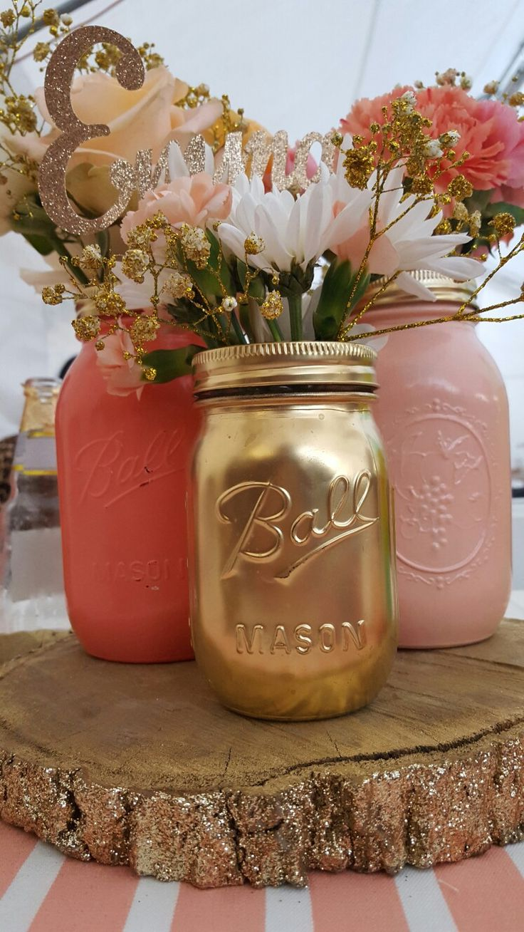 Baby shower centerpieces. glitter covered logs, mason jars,gold and coral shades, flowers,daisies,mini roses, glitter covers letters, diy ,gold covered baby spread.