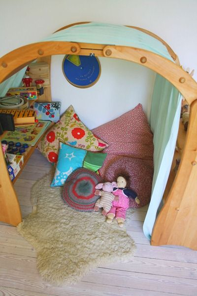 cozy play space with rug, dolls, pillows, and toys