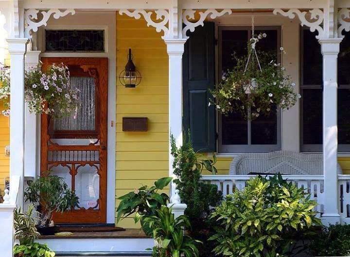Victorian Porch with ornate scroll woodwork at the top.