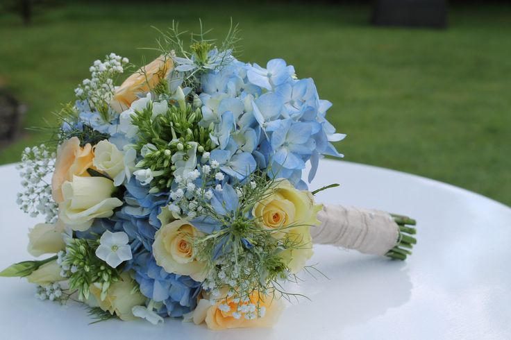 Bouquet of blue hydrangea, yellow roses, white spray roses, white gypsophila finished with linen wrap handle and pearls