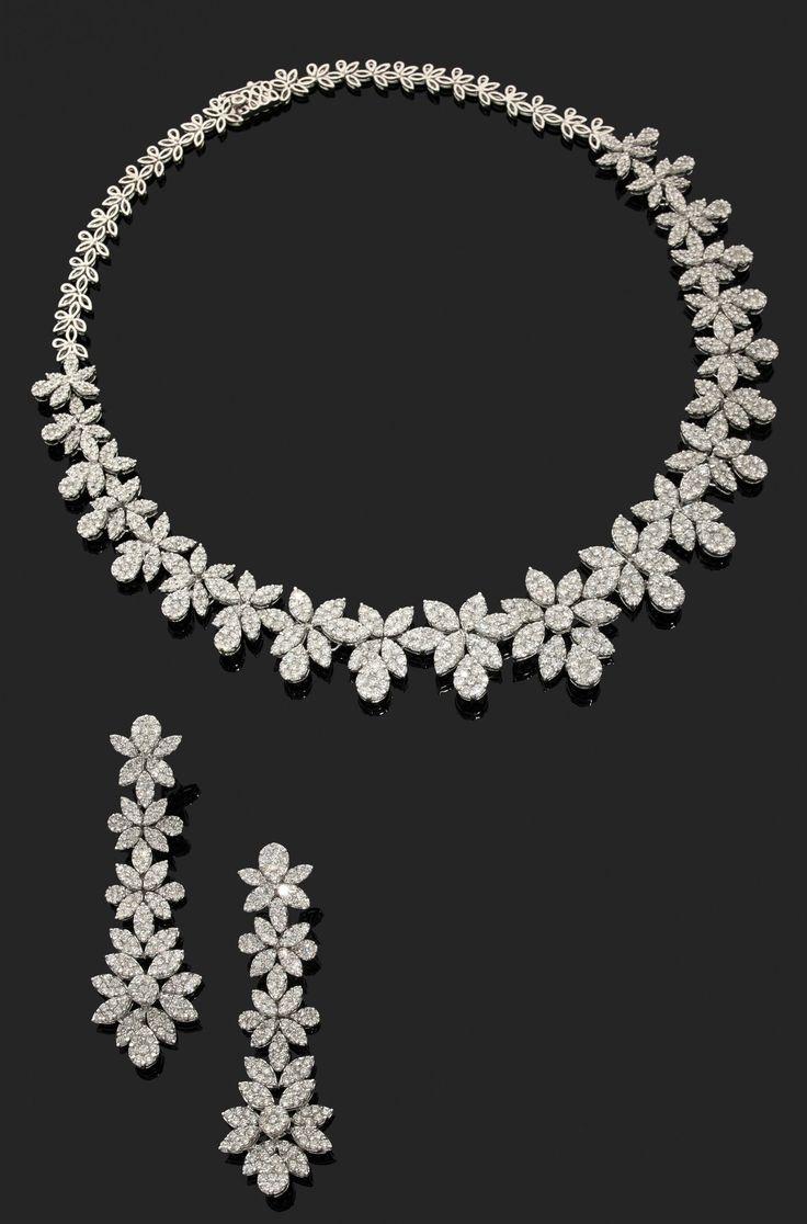 DEMI-PARURE en or gris 18k (750), articulée de chutes de fleurs aux pétales sertis de nombreux diamants taillés en brillant, composée d'une paire de pendants d'oreilles et d'un collier Long. du collier: 42 cm, Haut. des clips d'oreilles: 6.7 cm, Poids brut: 98.76 g  Estimation 18.000/20.000€