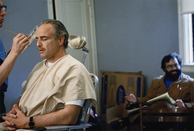 Marlon Brando consiguiendo el maquillaje hecho en el conjunto de El Padrino (1972). Franci Ford Coppola, el director, está sentado detrás de él.