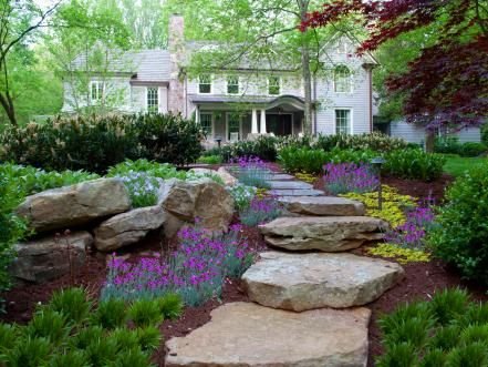 Freeform slabs of Tennessee fieldstone and Pennsylvania bluestone create a rustic pathway that enhances the cottage air of the house and grounds. Colorful perennials and groundcovers are sprinkled along the edges.