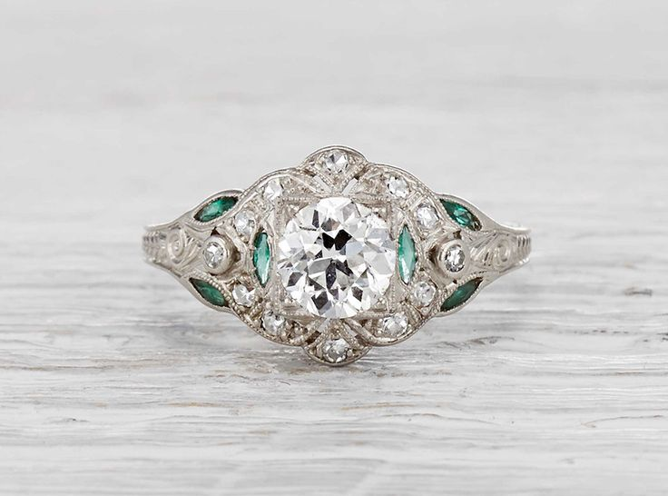 Antique late Edwardian engagement ring made in platinum and centered with a GIA certified 1.02 carat old European cut diamond with H color and VS2 color. Accented with single cut diamonds and emeralds. Circa 1920.