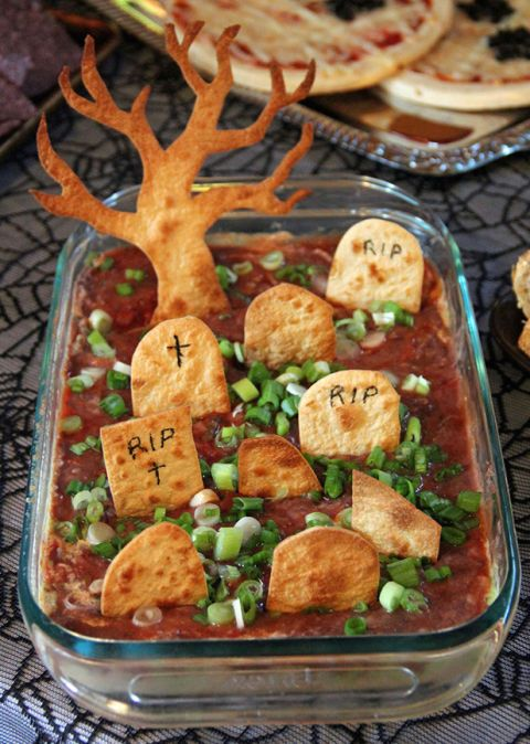 "Tortilla tombstones perfectly scoop up this Tex-Mex layered dip. Sprinkle on a little scallion ""grass"" for a truly gourmet final resting place. Click through for the recipe and more Halloween treats for this year's Halloween party."